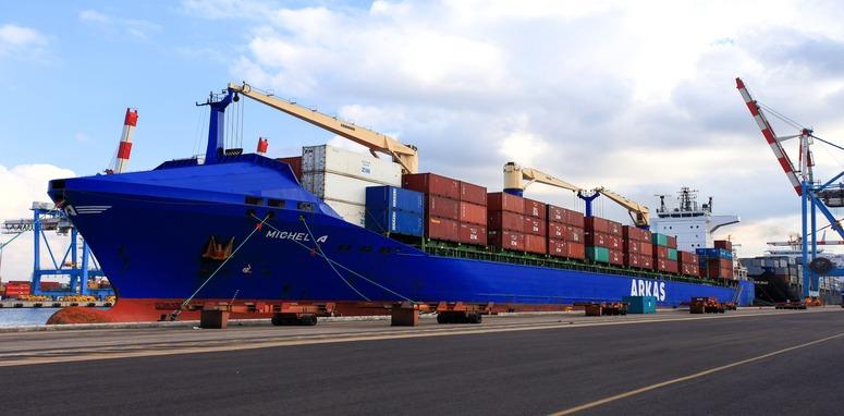 Haifa, Israel - February 2, 2016 : International Mega Container ship unloading containers on service trucks at Haifa's international port. with people.