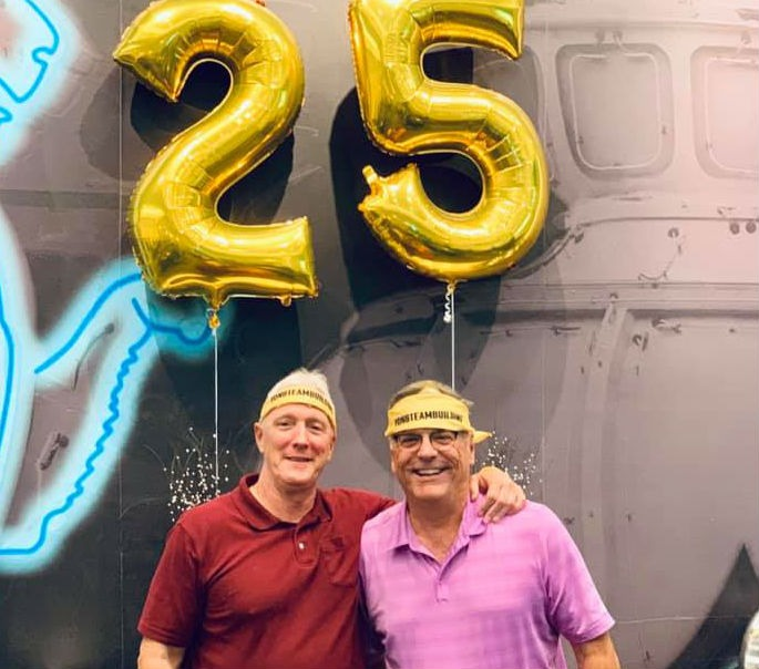 two men smiling with balloons